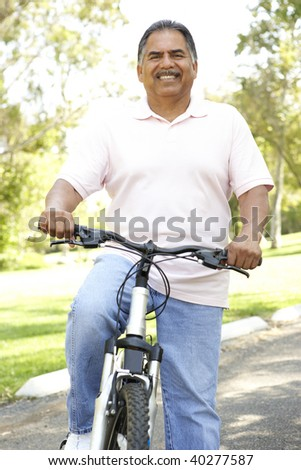 Senior Man Riding Bike In Park - stock photo