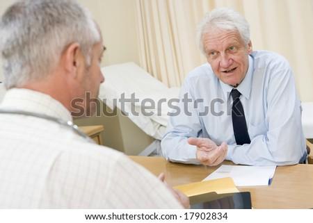 Senior man sat in doctors office - stock photo