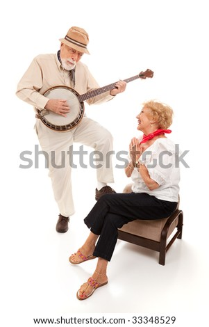 Senior man serenading his lady on his banjo.  Isolated on white.