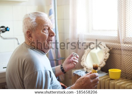 Senior man shaving his beard in bathroom in front of the mirror