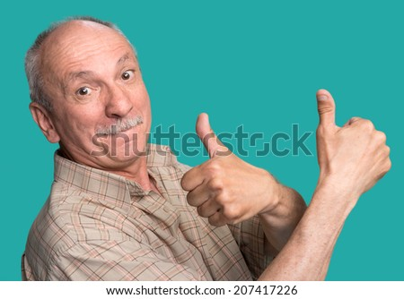 Senior man showing ok sign on blue background