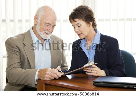 Senior man signing a contract in his attorney's office. - stock photo