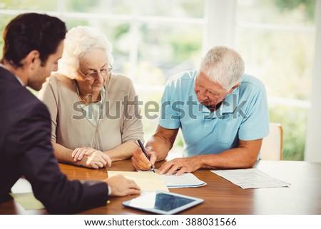 Senior man signing document at home - stock photo