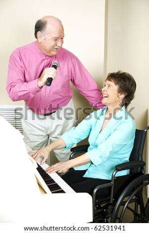 Senior man sings to a pianist in a wheelchair.