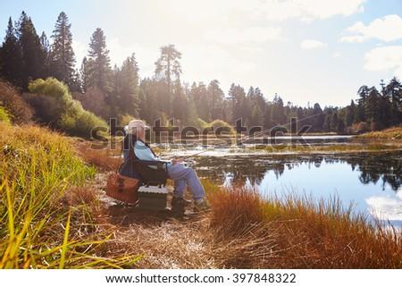 Senior man sits fishing, Bluff Lake, California - stock photo