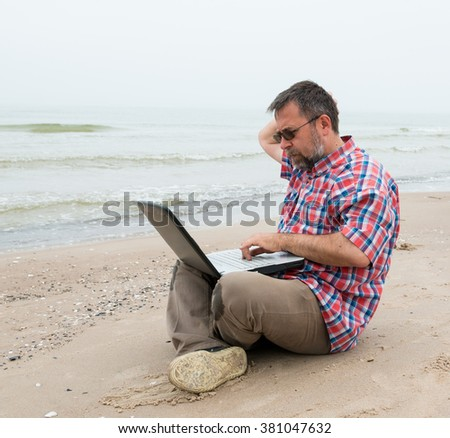 Senior man sitting at the beach with  laptop on a foggy day
