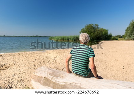 Senior man sitting at tree trunk in landscape with river - stock photo
