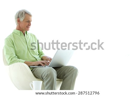 Senior man sitting in a chair and using laptop on knees - stock photo