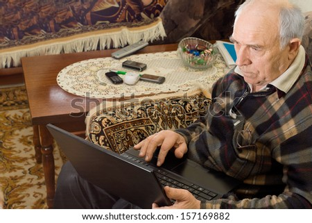 Senior man sitting in a comfortable armchair in his living room working on a laptop computer surfing the internet - stock photo
