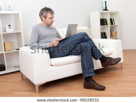 Senior man sitting in sofa at home and using laptop - stock photo