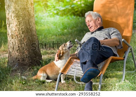Senior man sitting in sunbed in park and cuddling cute dog - stock photo
