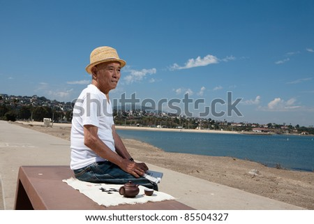 senior man sitting on a bench and looking at the beach landscape