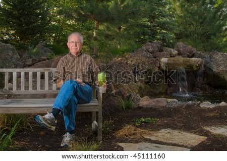 Senior man sitting on a bench by a man-made pond and waterfall