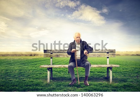 senior man sitting on a bench outdoor - stock photo