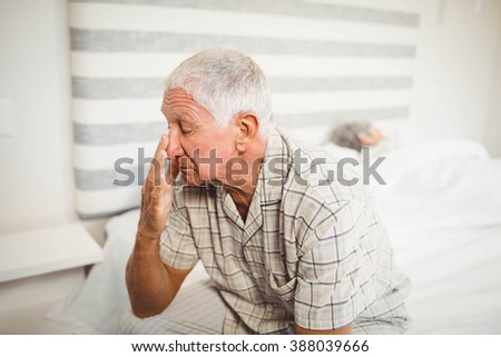 Senior man sitting on bed in bedroom
