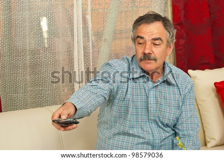 Senior man sitting on couch in living room and opening tv with remote control - stock photo