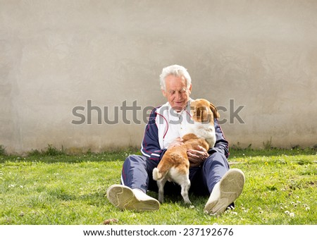 Senior man sitting on grass with his dog - stock photo