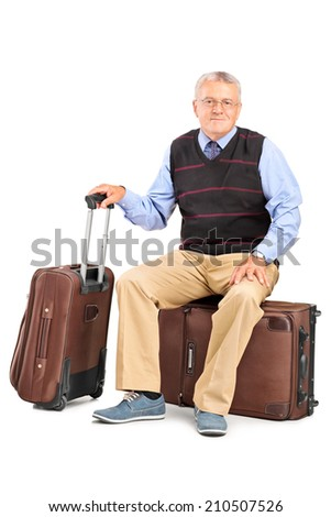 Senior man sitting on his baggage isolated on white background - stock photo