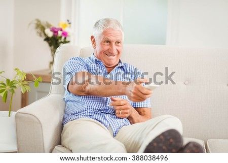 Senior man sitting on sofa and watching television in living room - stock photo