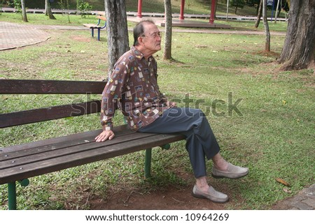 Senior man sitting on the bench in the park - stock photo