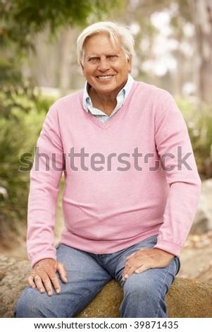 Senior Man Sitting On Wall - stock photo