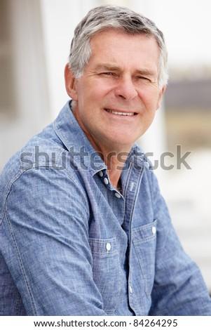 Senior man sitting outdoors - stock photo