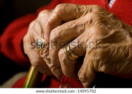Senior Man Sitting with hands on Cane.  Rings in forefront. - stock photo