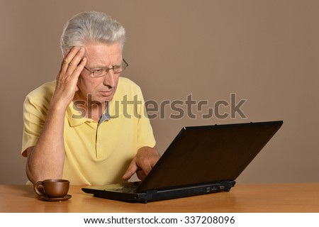 Senior man sitting with laptop on table