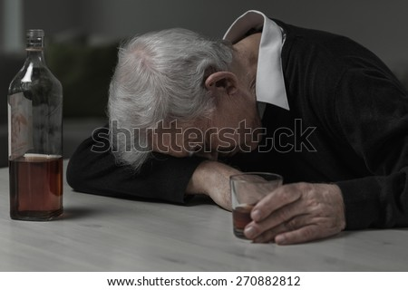 Senior man sleeping after drinking too much alcohol - stock photo
