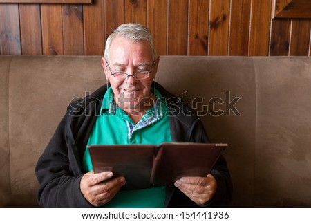 Senior man smiling and reading a restaurant menu ready to order food - stock photo