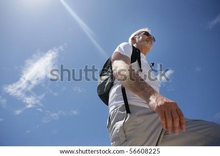 Senior man smiling with a backpack and sunglasses - stock photo