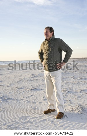 Senior man standing on beach with hands on hips - stock photo
