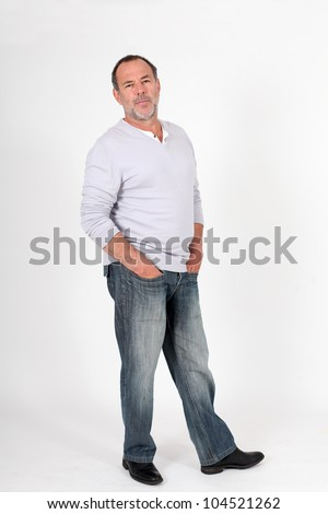 Senior man standing on white background with hands in pocket - stock photo
