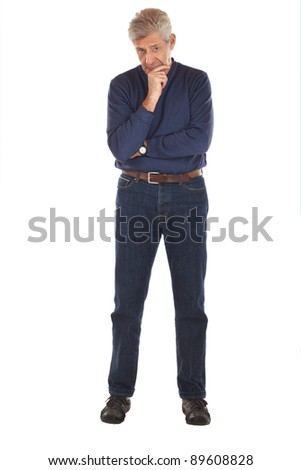Senior man stands, arms crossed, with one hand on chin in thoughtful full length pose. He faces forward, wearing dark blue jeans and v-necked long sleeved shirt. Vertical format isolated on white. - stock photo