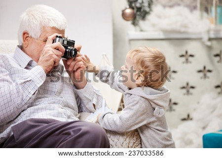 Senior man taking photo of his toddler grandson at Christmas time - stock photo