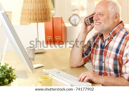 Senior man talking on cellphone, using computer, smiling, looking at screen at home.? - stock photo