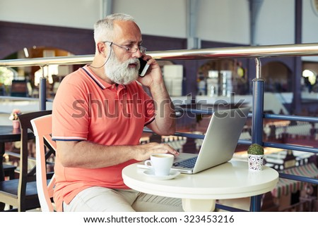 senior man talking on the phone and looking at laptop in cafe - stock photo