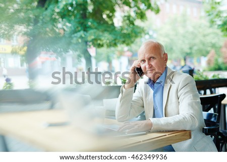 Senior man talking on the phone at cafe outdoors