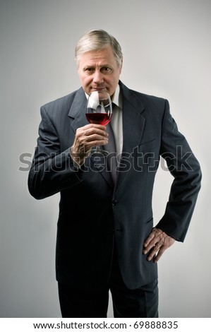 Senior man tasting a glass of wine - stock photo