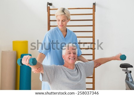 Senior man training with his therapist in fitness studio
