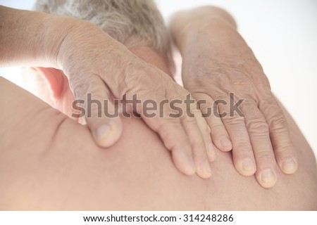 Senior man tries to reach the painful area on his back. - stock photo