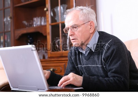 Senior man typing on a laptop - stock photo