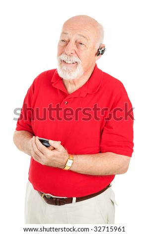 Senior man using a hands-free set to talk on his cellphone.  Isolated on white.