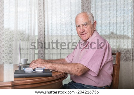 Senior man using a laptop at home - stock photo