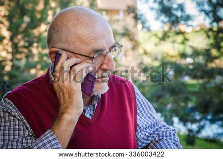SENIOR MAN USING CELL PHONE ON A PARK BACKGROUND, IN SPAIN - stock photo
