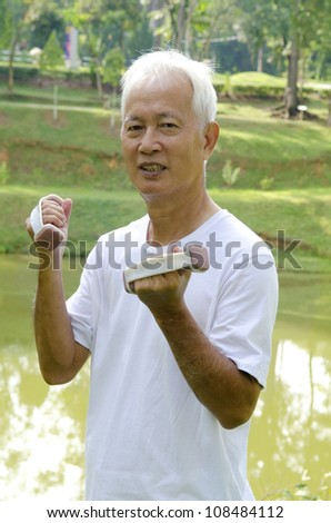 Senior man using dumbells on outdoor