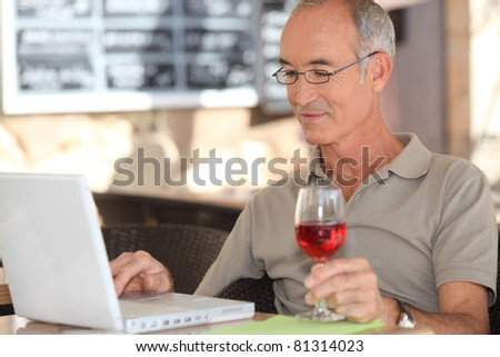 Senior man using his laptop in a cafe - stock photo