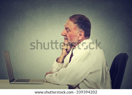 Senior man using laptop computer reading email news. E-learning concept  - stock photo