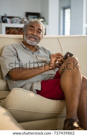 Senior man using mobile phone in the living room at home