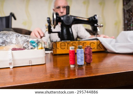 Senior Man Using Old Fashioned Manual Sewing Machine to Mend Clothing with Focus on Colorful Spools of Thread in Foreground - stock photo